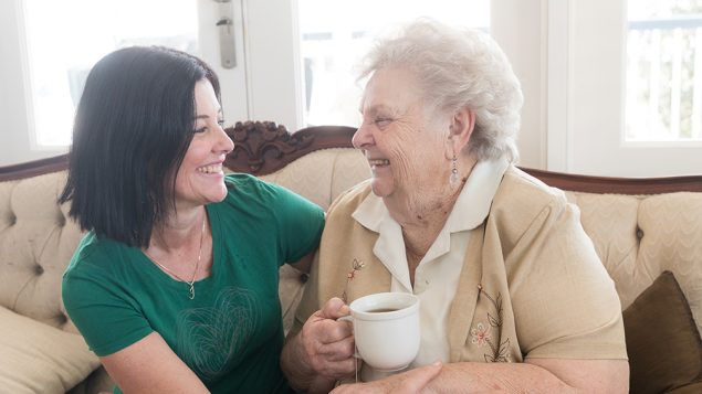 Caregiver sitting on the couch with senior lady