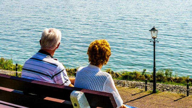 Elderly couple sitting on a bench looking out over the water